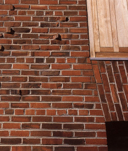 Figure 9: Exeter Library, detail of exterior façade.  Note the miscut bricks casting shadows and the jack arch that seamlessly widens the openings.